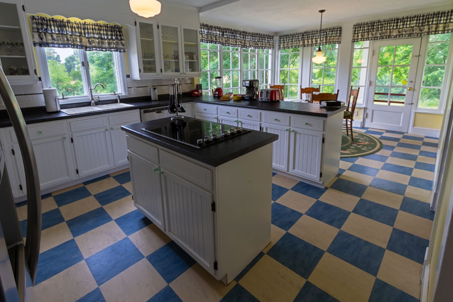 vine cottage kitchen with white cupboards and blue tile in natural bridge, virginia