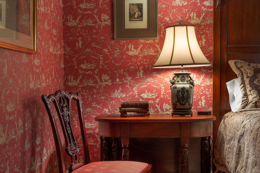 long branch guestroom with antique nightstand lamp and chair next to red wall paper at the inn at forest oaks in natural bridge virginia