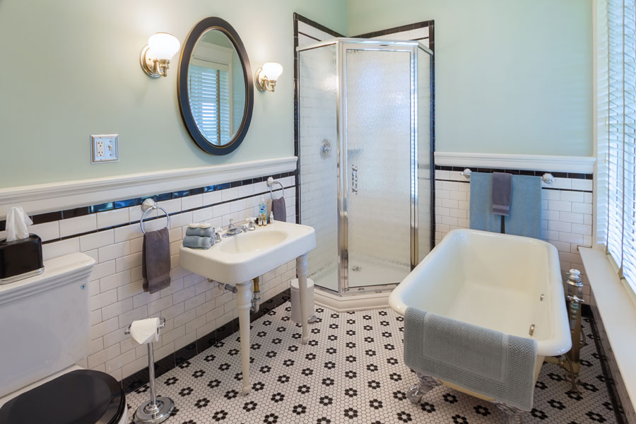 milburn guestroom bathroom with white tile shower pedestal sink and clawfoot tub at the inn at forest oaks in natural bridge virginia