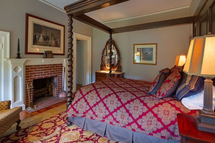 stratford guestroom with ornate antique bed and fireplace at the inn at forest oaks in natural bridge virginia