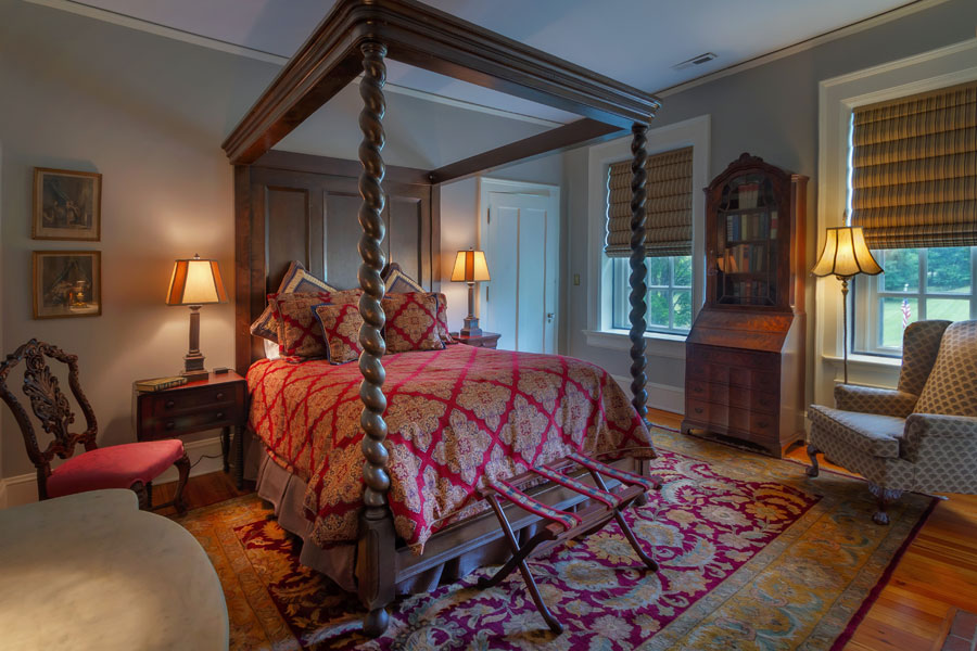 stratford guestroom with antique bed table and chairs at the inn at forest oaks