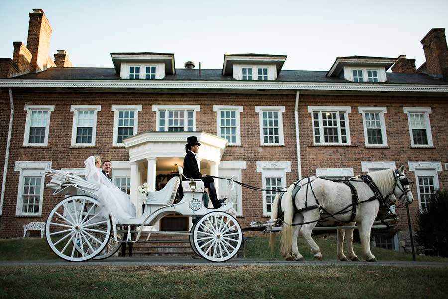 wedding coach with horses in front of the inn at forest oaks in virginia